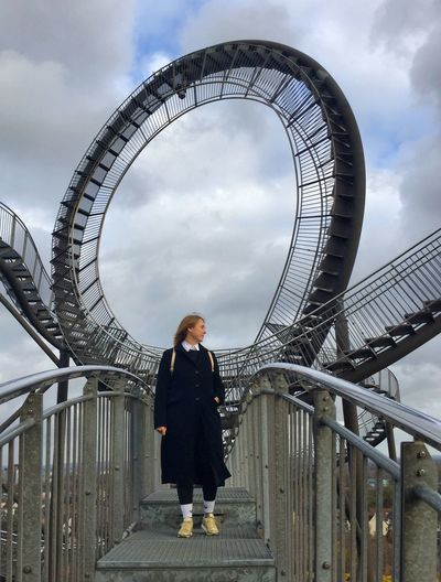 Woman standing on bridge against spiral staircases