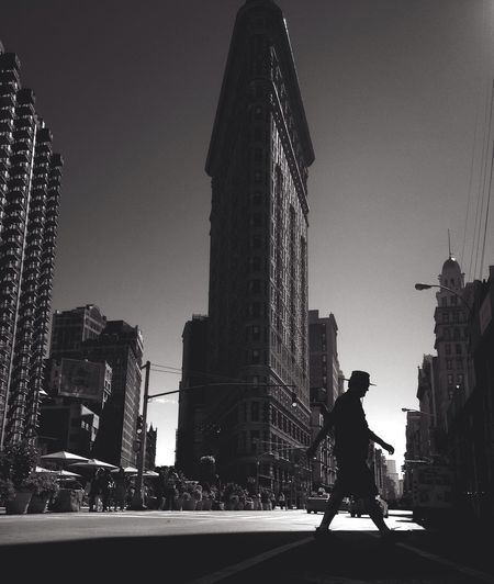 Low angle view of man walking against flatiron building in city