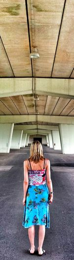 Rear view full length of woman standing below bridge