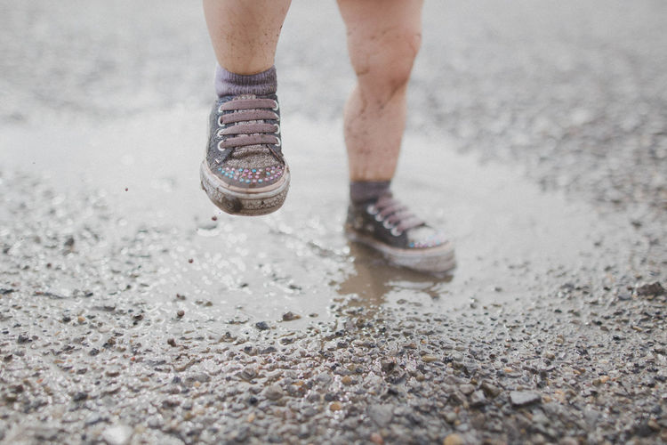 Low Section Of Child Walking On Puddle