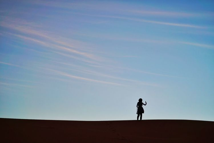 Silhouette woman in sahara desert against clear sky