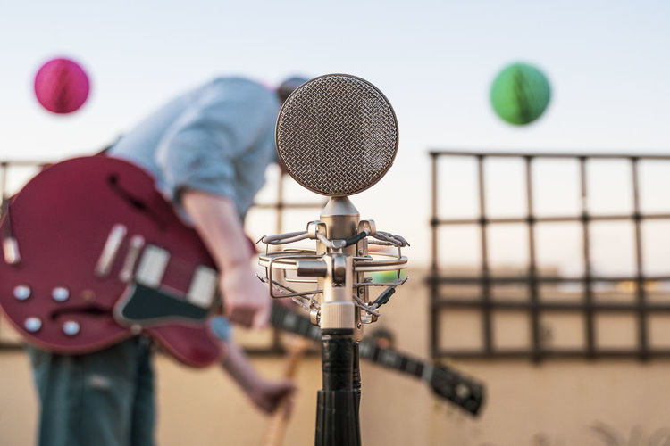 Close-up of microphone with man standing with guitar standing outdoors