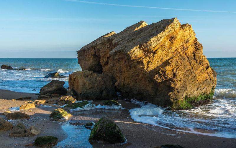 Rocks on beach by sea against sky