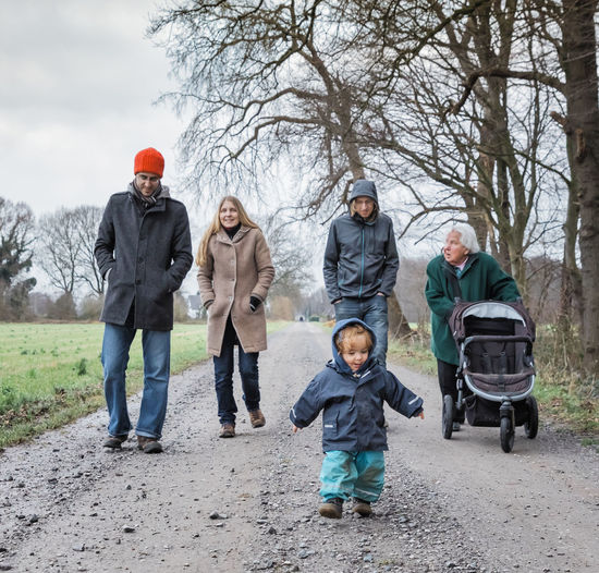 Family Walking On Footpath During Winter