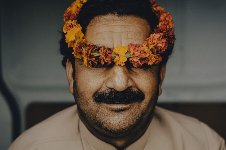 Close-up of man wearing floral garland on head