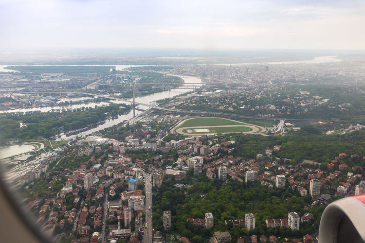 Belgrade, Serbia, May 01, 2019 : View of the Belgrade city and Danube river from the illuminator of the flying plane. Belgrade city in Serbia Belgrade,Serbia Transportation Day Nature Airplane Danube River Suburb Travel Destinations Tourism Destination Landscape Beutiful  Trip Water Passenger Flight City Vacation Europe Aerial View Departure Baggage Arrival Urban Illuminator Sky And Clouds