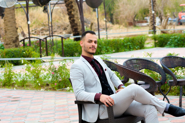 Full length portrait of confident businessman sitting on chair at patio