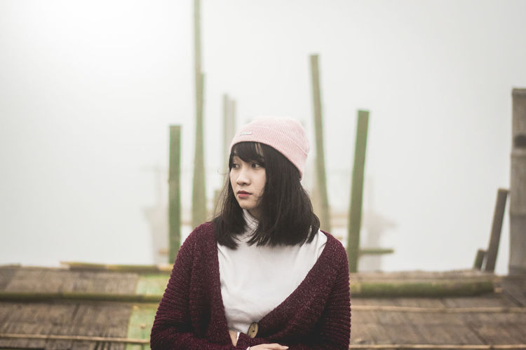 Young woman looking away while sitting on pier against sky
