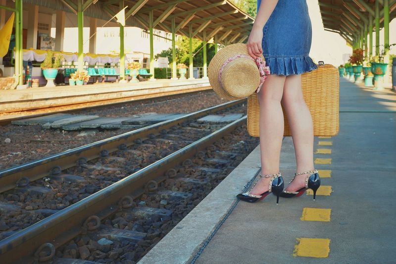 Low section of young female traveler holding vintage hat and bamboo suitcase waiting for train on railroad platform at station, lifestyle in travel concept Traveler Travel Holding Bamboo Suitcase Hat Waiting For The Train Space Lifestyle Female Young Vintage Outdoor Urban City Low Section Standing Women Railroad Track Railroad Station Platform Railroad Platform Railroad Station Public Transportation Tourism High Heels