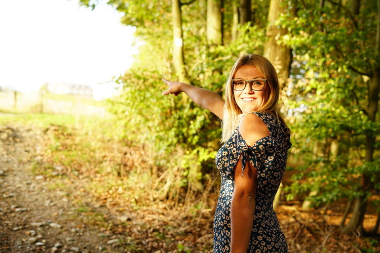 Portrait of smiling young woman gesturing while standing against trees in forest