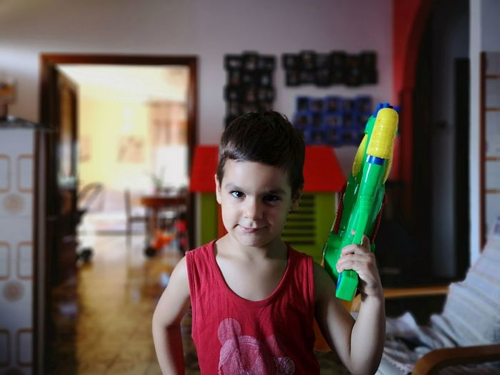 Portrait of boy holding squirt gun while standing at home
