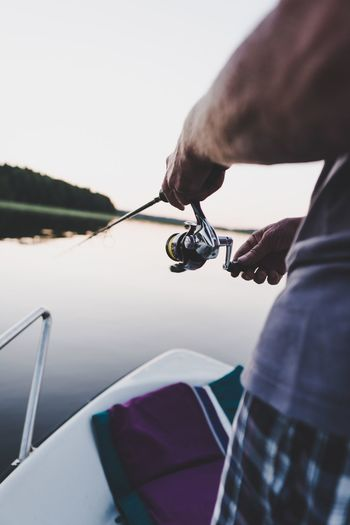 Midsection of man fishing in lake during sunset