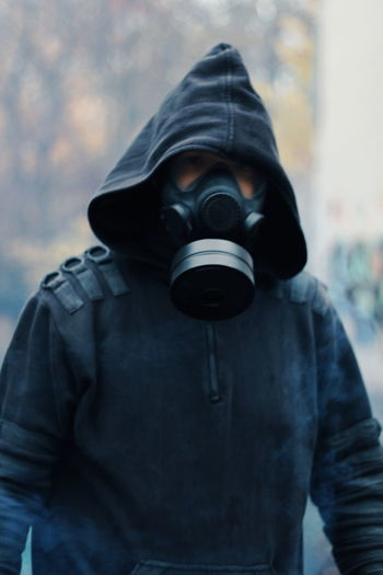 Man wearing gas mask standing outdoors
