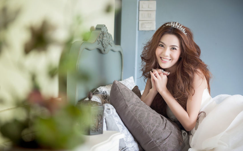 Portrait of smiling young bride wearing tiara on bed at home