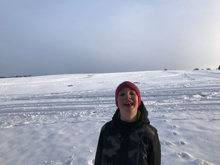 Portrait of smiling boy standing on snow covered landscape against sky during sunset