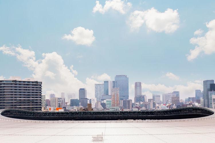 Aerial shot dense tokyo city buildings over shinjuku city, tokyo olympic stadium