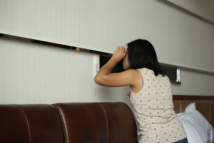 Side view of woman standing by wall at home