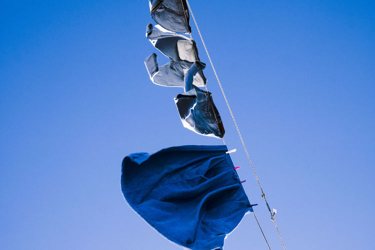 Low angle view of laundry hanging on clothesline against clear blue sky