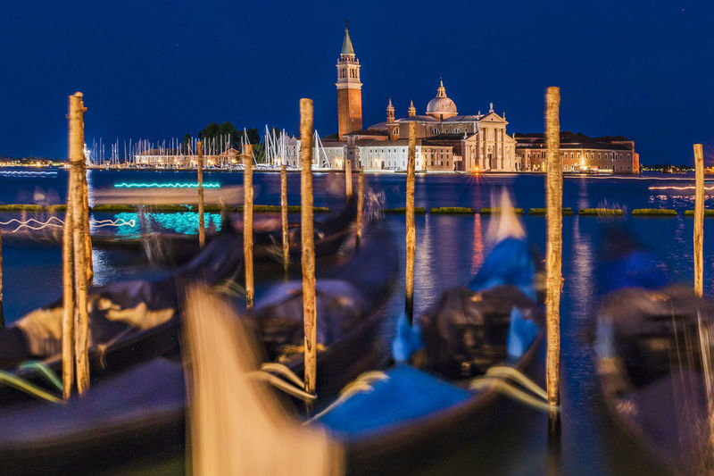 Illuminated city by canal at night
