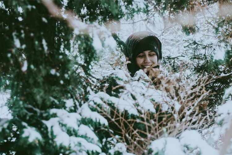 Smiling Woman Amidst Snow Covered Tree In Forest