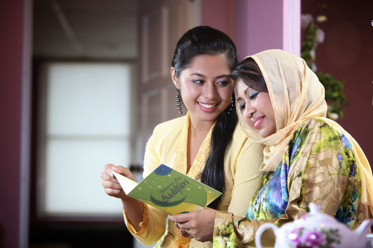 Mother and daughter reading greeting card at home during celebration