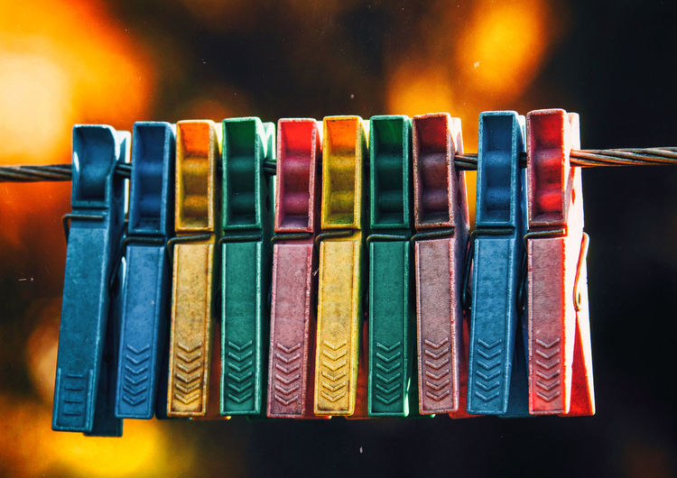 Close-up of colorful clothespins attached on clothesline
