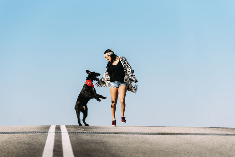 Woman with dog and skateboard against clear blue sky
