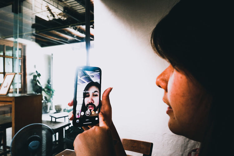 Portrait of woman photographing through smart phone