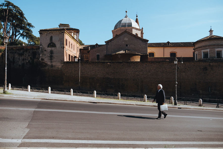 Urban Loneliness | Building Exterior Businessman Clear Sky Day Loneliness One Man Only One Person Outdoors Pain Real People Road Rome Street Street Photography Streetphotography Suitcase Uphill Walking Walking Around Investing In Quality Of Life