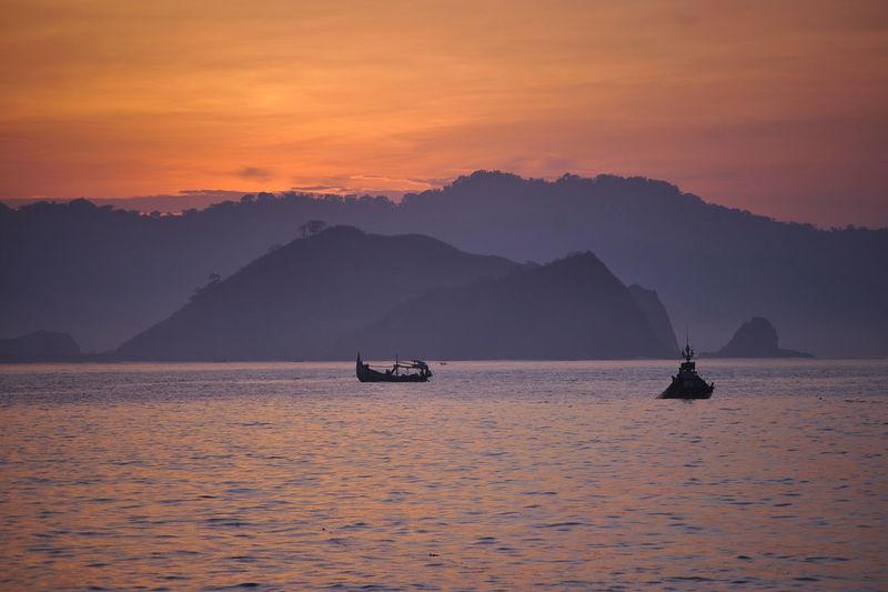 Boats on sea against orange sky