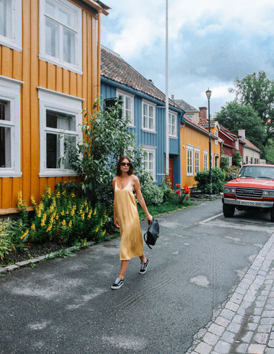 Building Exterior Architecture Full Length One Person City Day Street Building Casual Clothing Running Nature Cloud - Sky Domestic Animals Walking One Animal Outdoors Woman Girl Dress Yellow Colorful Houses Trondheim Norway Bergen