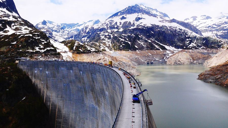 Snow covered mountains with dam in foreground