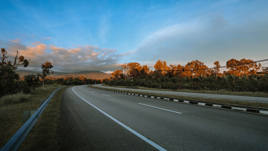 Highway in Malaysia sunset scenery Road Transportation Sky Direction The Way Forward Tree Cloud - Sky Plant Symbol Marking Road Marking No People Sign Nature Beauty In Nature Tranquil Scene Tranquility Diminishing Perspective Scenics - Nature Non-urban Scene Outdoors Dividing Line