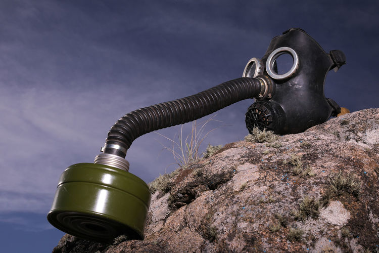 Low angle view of gas mask on rock against sky