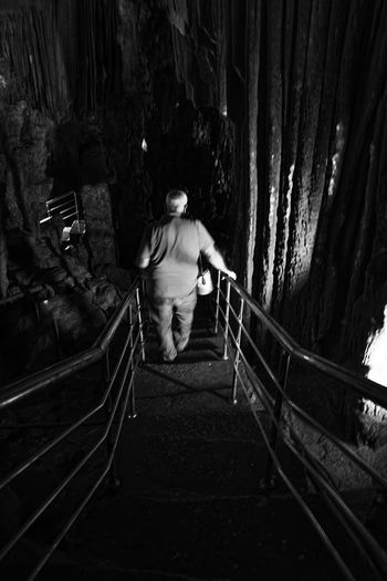 Following a Path Adult Astim Caves Cave Curves And Lines Day Footbridge Full Length Metal Moving Forward  One Person Outdoors Path Pathway People Railing Railings Real People Rear View Stairs Steps And Staircases The Way Forward Walking Winding Stairs