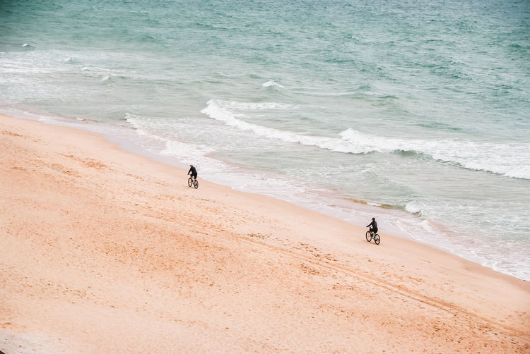 High Angle View Of People Riding Bicycle On Beach