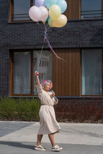 Full length of woman with balloons standing against building