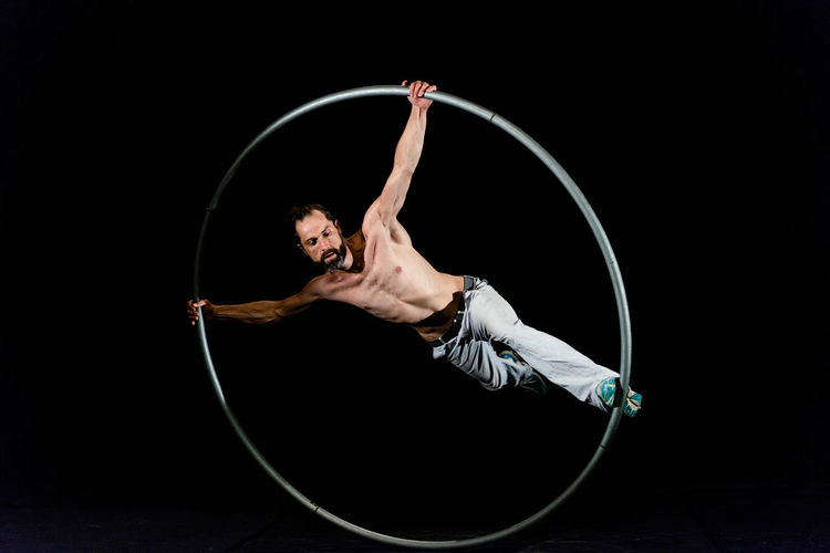 Circus Acrobat Adult Agility Arms Raised Arts Culture And Entertainment Balance Black Background Circus Dancing Exercising Flexibility Full Length Holding Human Arm Indoors  Motion One Person Performance Plastic Hoop Skill  Studio Shot Young Adult