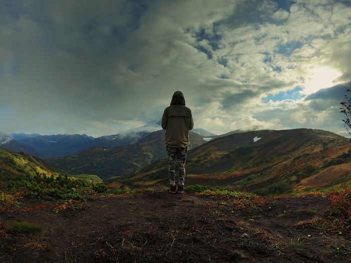 Rear view of young man standing on mountain against cloudy sky