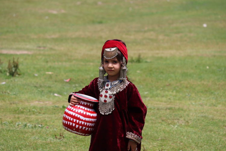 Portrait of girl in traditional clothing holding container while standing on field