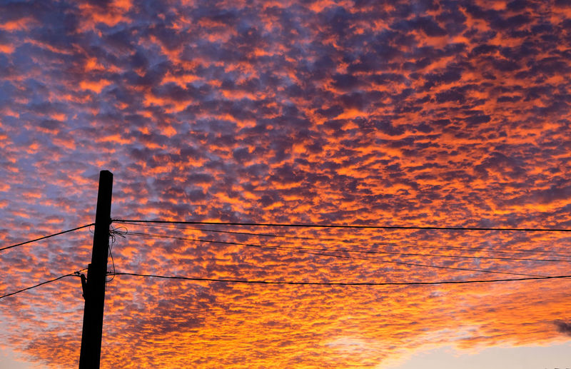 Low angle view of silhouette electricity pylon against orange sky