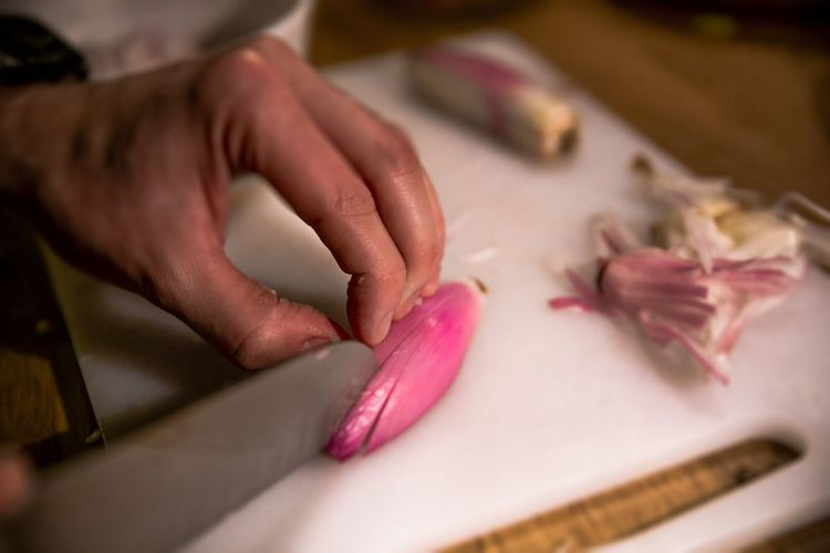 Close-Up Of Hand Chopping Onion