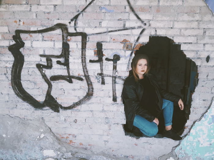 Full length of young woman sitting on wall