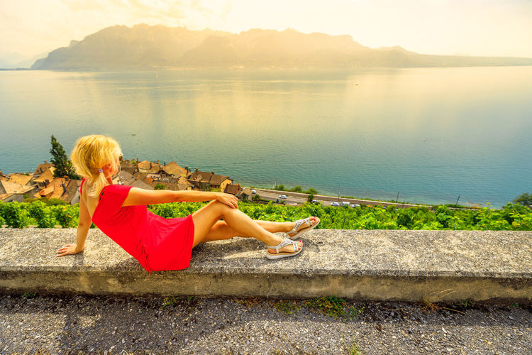 Woman sitting by lake against mountain