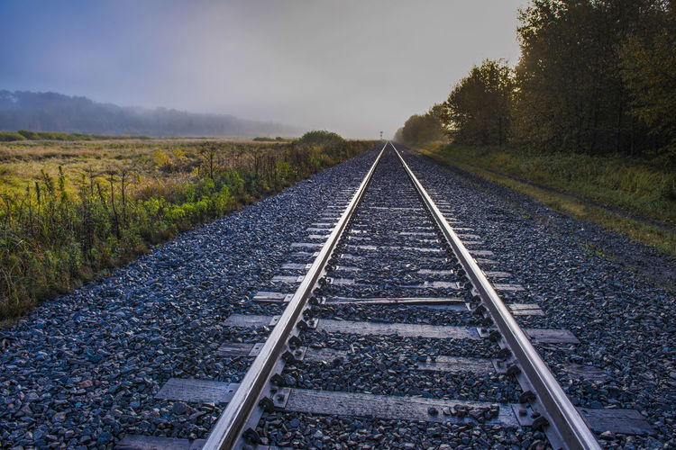 CANADA. Railroad tracks towards infinity Nature Landscape Blue Long Misty Morning Tranquility Wet Track Transportation Direction Infinity Parallel Gravel Pebble Railroad Track No People Uncertainty  Railway Sleepers Rail Transportation The Way Forward Diminishing Perspective Scenics - Nature vanishing point Tranquil Scene Land
