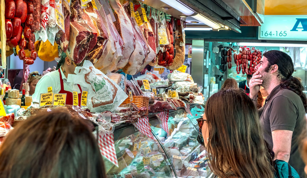 Malaga, Spain - May 05, 2018. Customers at the Spanish specialties fom Ataranzanas Central Market, Malaga, Spain Ataranzanas Cheese! Ham Jamon Malaga SPAIN Spanish Food Adult Business Buying Choice Consumerism Customer  Food Food And Drink For Sale Fujifilm Group Of People Iberic Pork Indoors  Jamón Ibérico Market Market Stall Meat Men People Real People Retail  Retail Display Roberto Sorin Sausage Shopping Spanish Culture Store Variation Women The Photojournalist - 2018 EyeEm Awards The Street Photographer - 2018 EyeEm Awards
