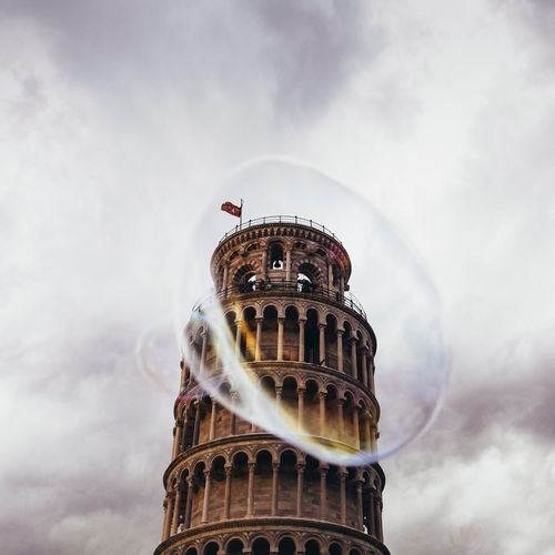 Leaning Tower Of Pisa Seen Through Bubbles Against Cloudy Sky