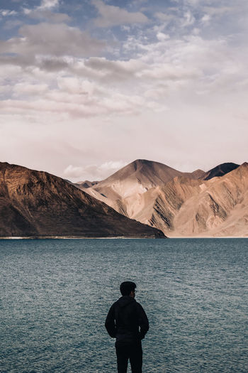Rear view of silhouette man standing at lakeshore against mountains