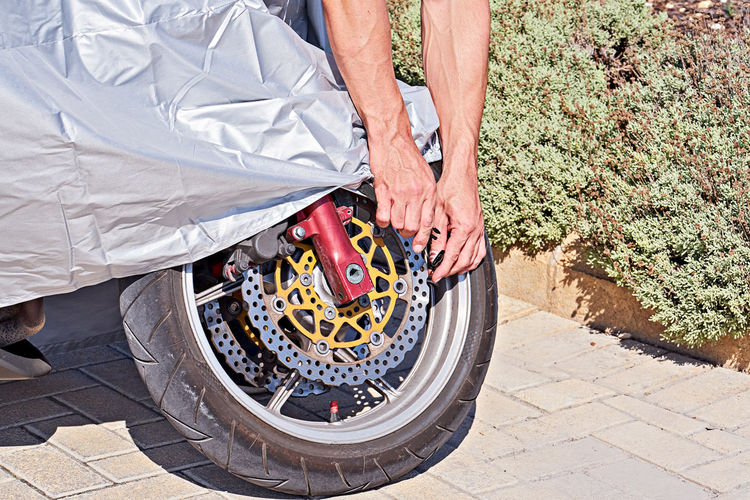 Cropped hands of man repairing motorcycle tire