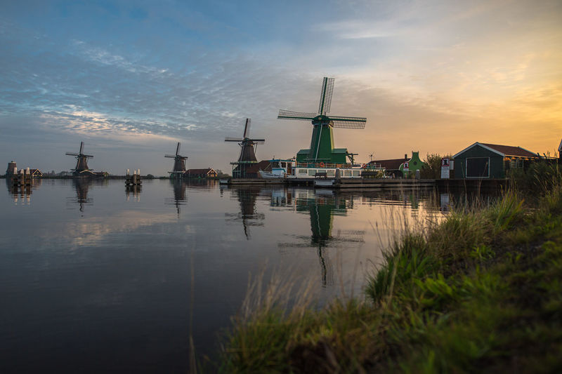 Lake against traditional windmills in town during sunset